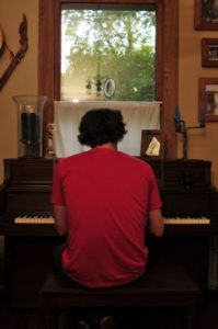 Caleb Elliot at piano at Bonne Terre Main House